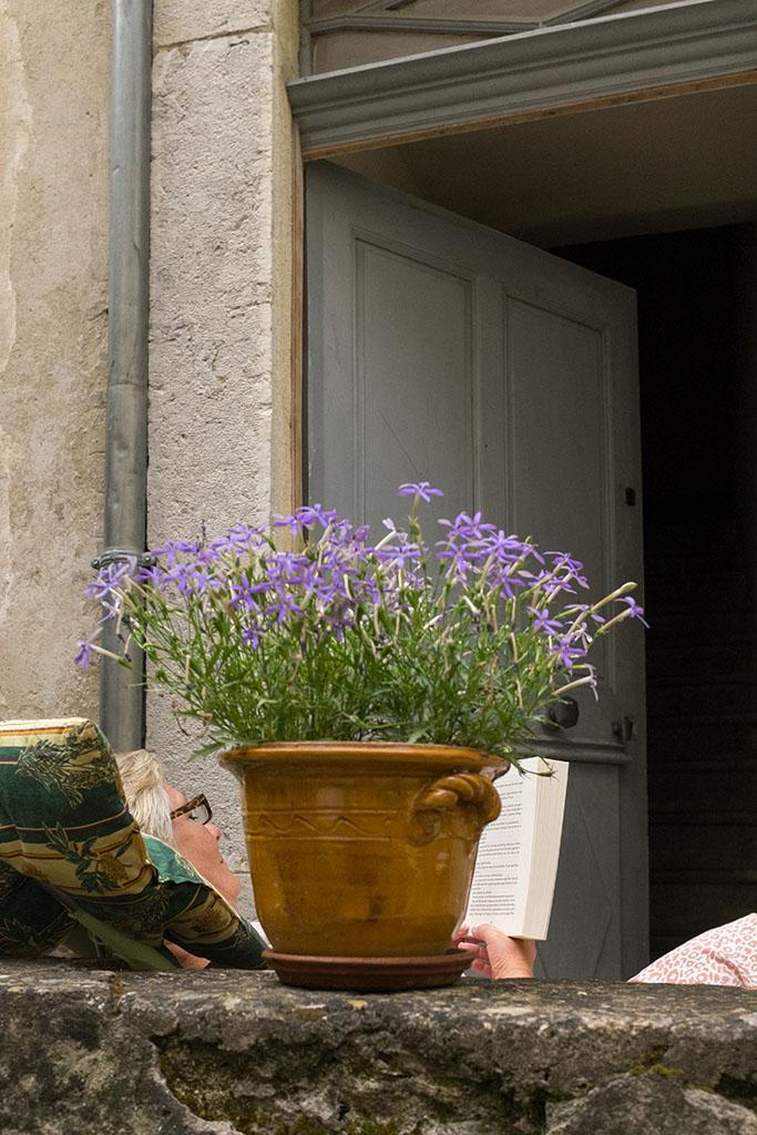 Une habitante lit devant chez elle.